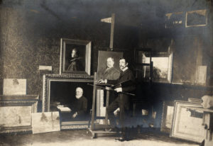 T.C. Steele standing with his paintings inside Tinker House